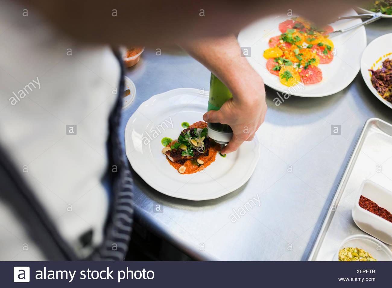 Chef chapado con salsa de alimentos en cocina comercial Imagen De Stock