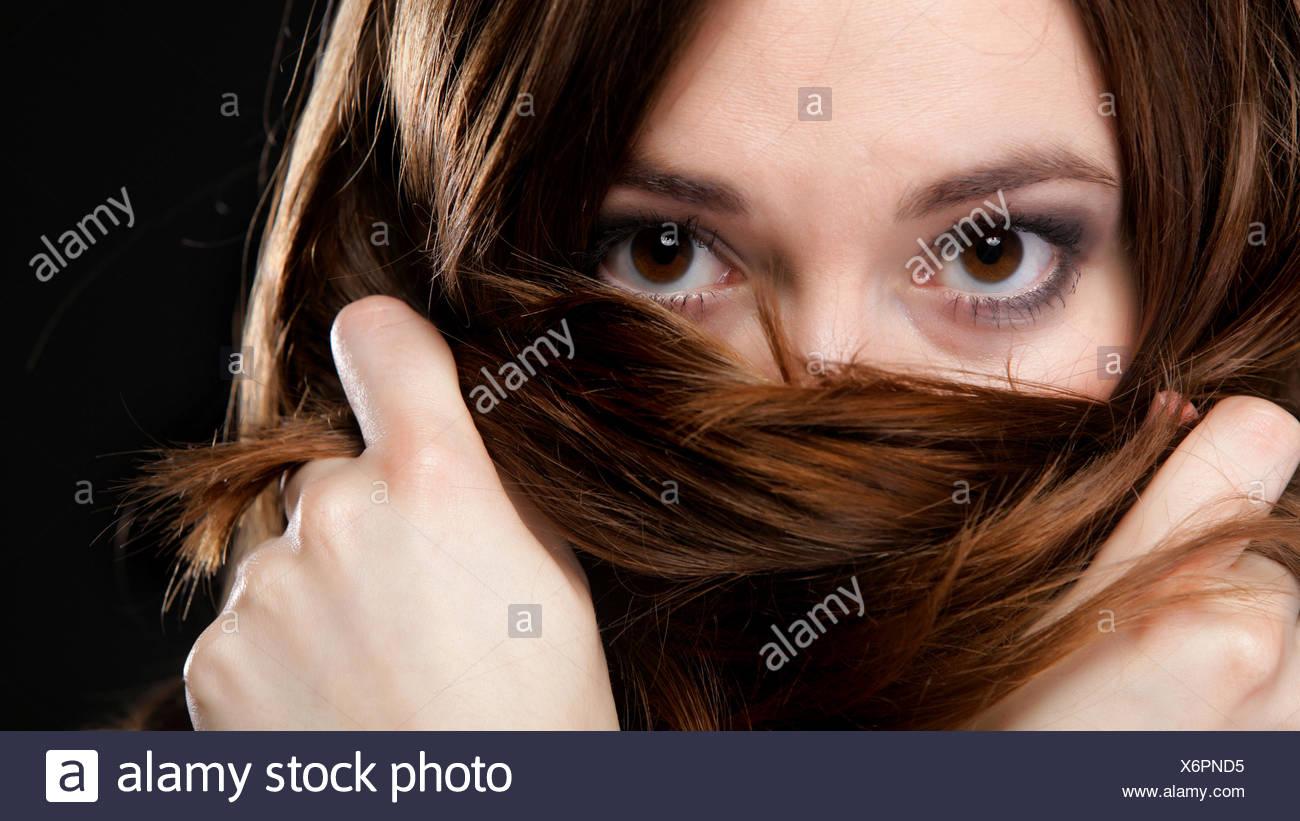 Closeup mujer cubre el rostro por largos pelos marrones Foto de stock