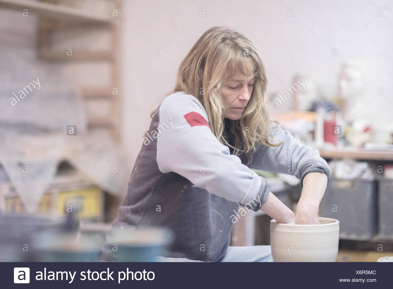 Hembra elevando una vasija de barro de alfarero rueda de alfarería Imagen De Stock