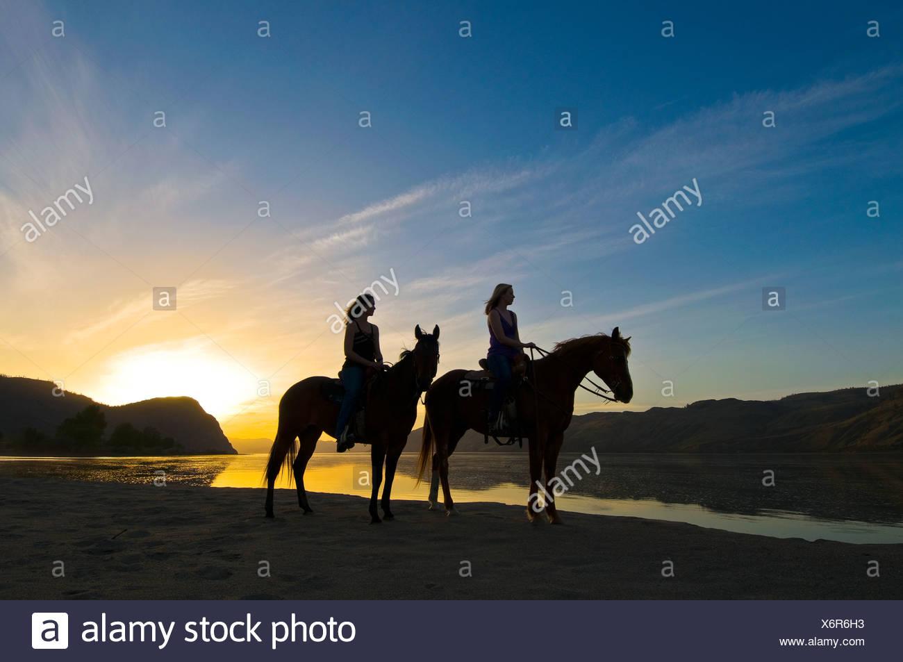 Dos mujeres jóvenes gozan de impresionantes vistas del atardecer caballos Imagen De Stock
