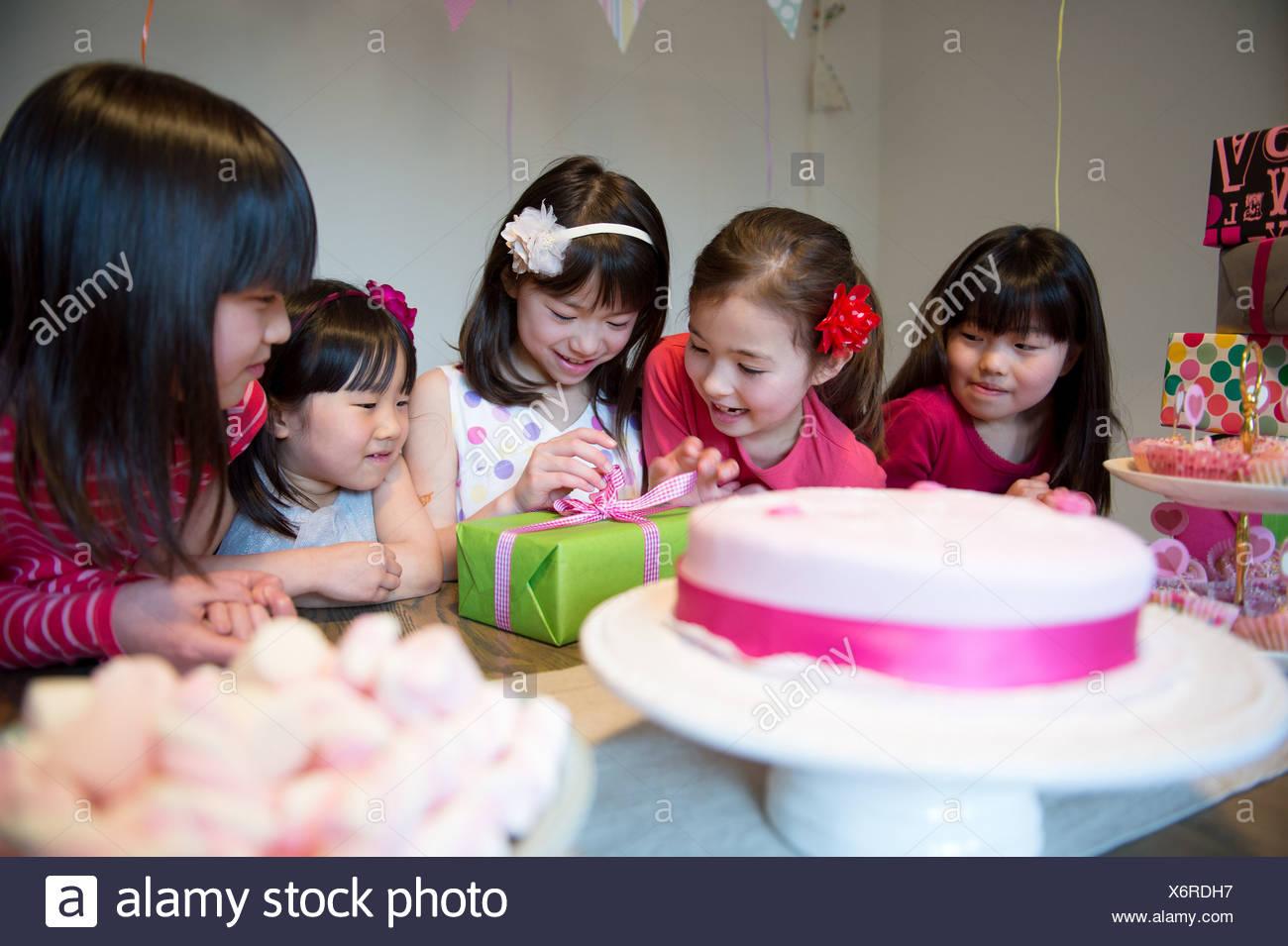 Chica desembalaje de regalo de cumpleaños en parte Imagen De Stock