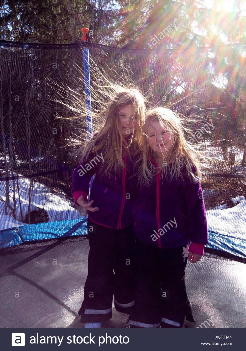 Suecia, dos niñas (6-7 años, 8-9 años) en el trampolín con la electricidad estática del pelo Imagen De Stock