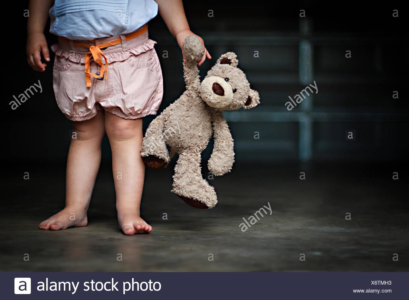 Bajo la sección de una chica sujetando su osito de peluche Imagen De Stock
