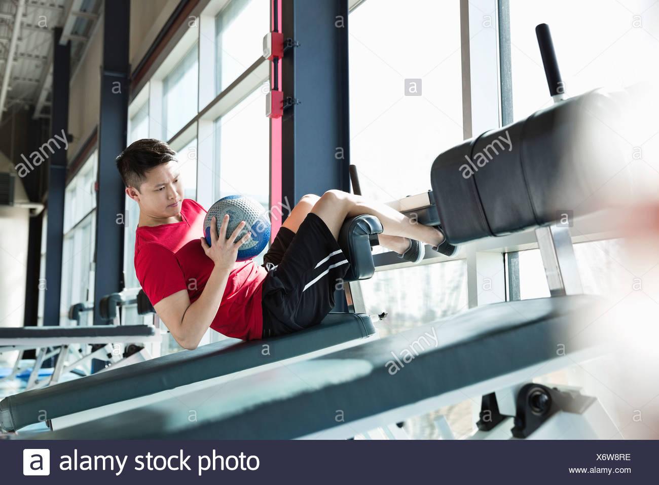 El hombre ejerciendo con balón medicinal en el gimnasio Imagen De Stock