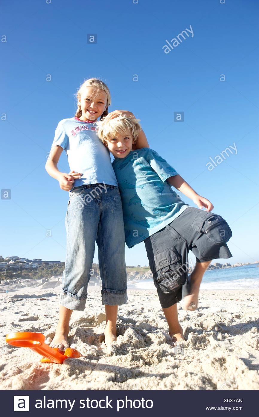 Niño y niña de 6 8 7 9 pie en playa chica sonriente niño recostado en ángulo de visión baja vertical Imagen De Stock