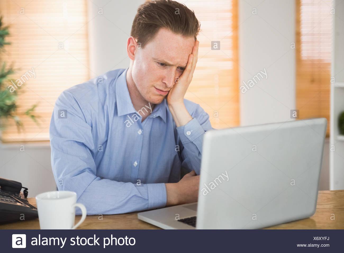 Empresario temeroso mirando a su portátil. Foto de stock