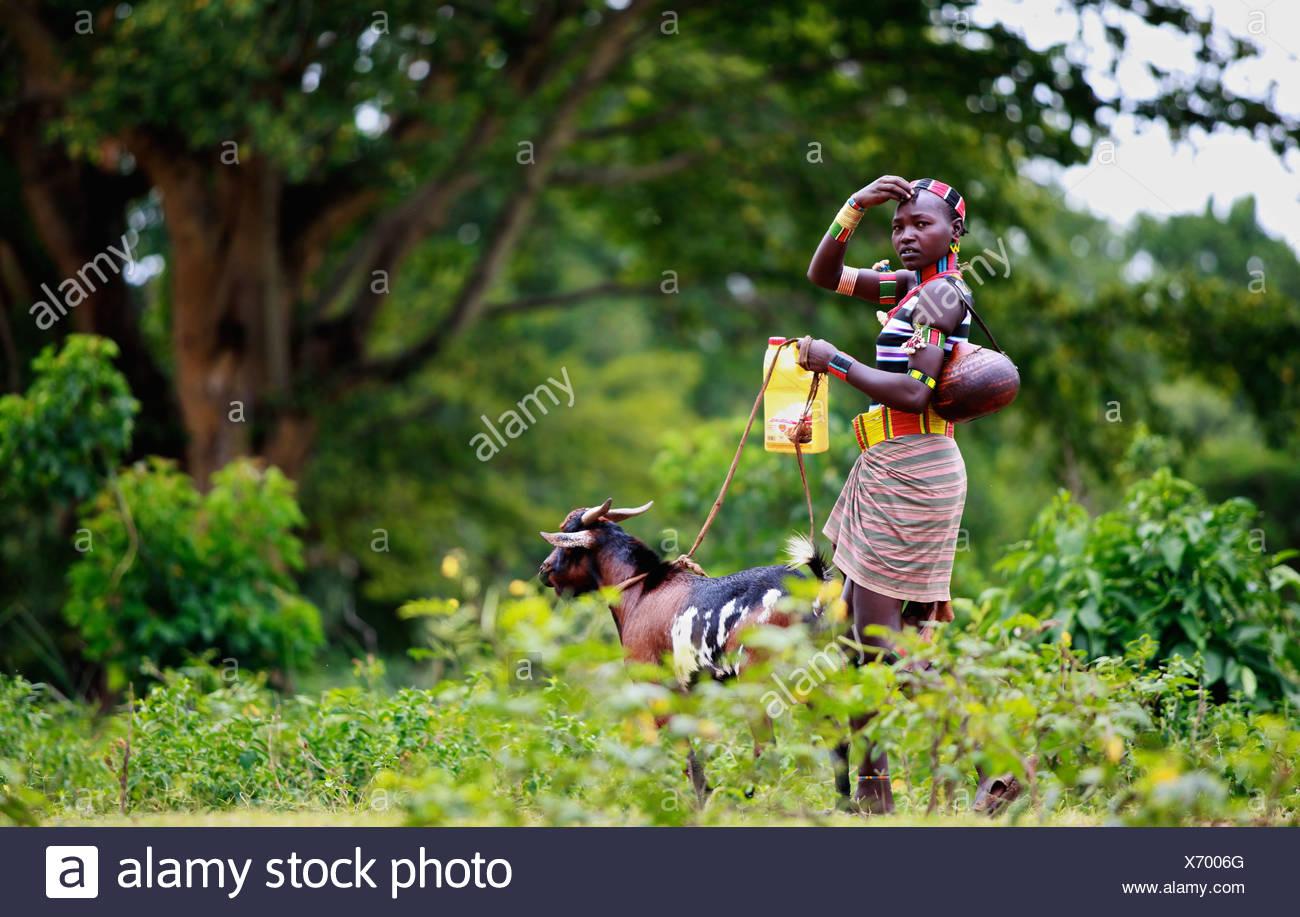 Joven Hamar tribal chica caminando con una cabra a través del bosque. Imagen De Stock