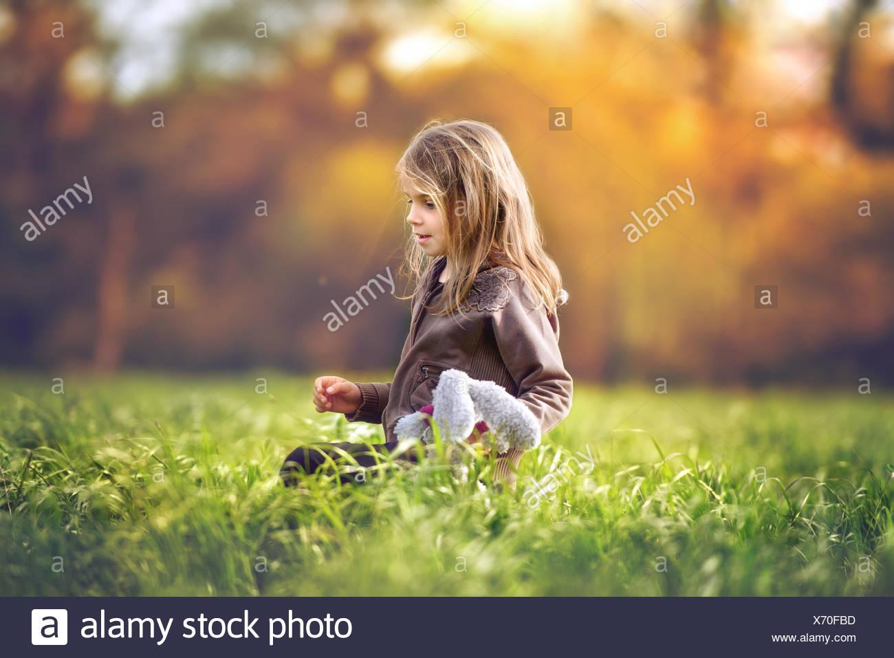 Chica sentada en un campo sosteniendo un juguete blando Imagen De Stock