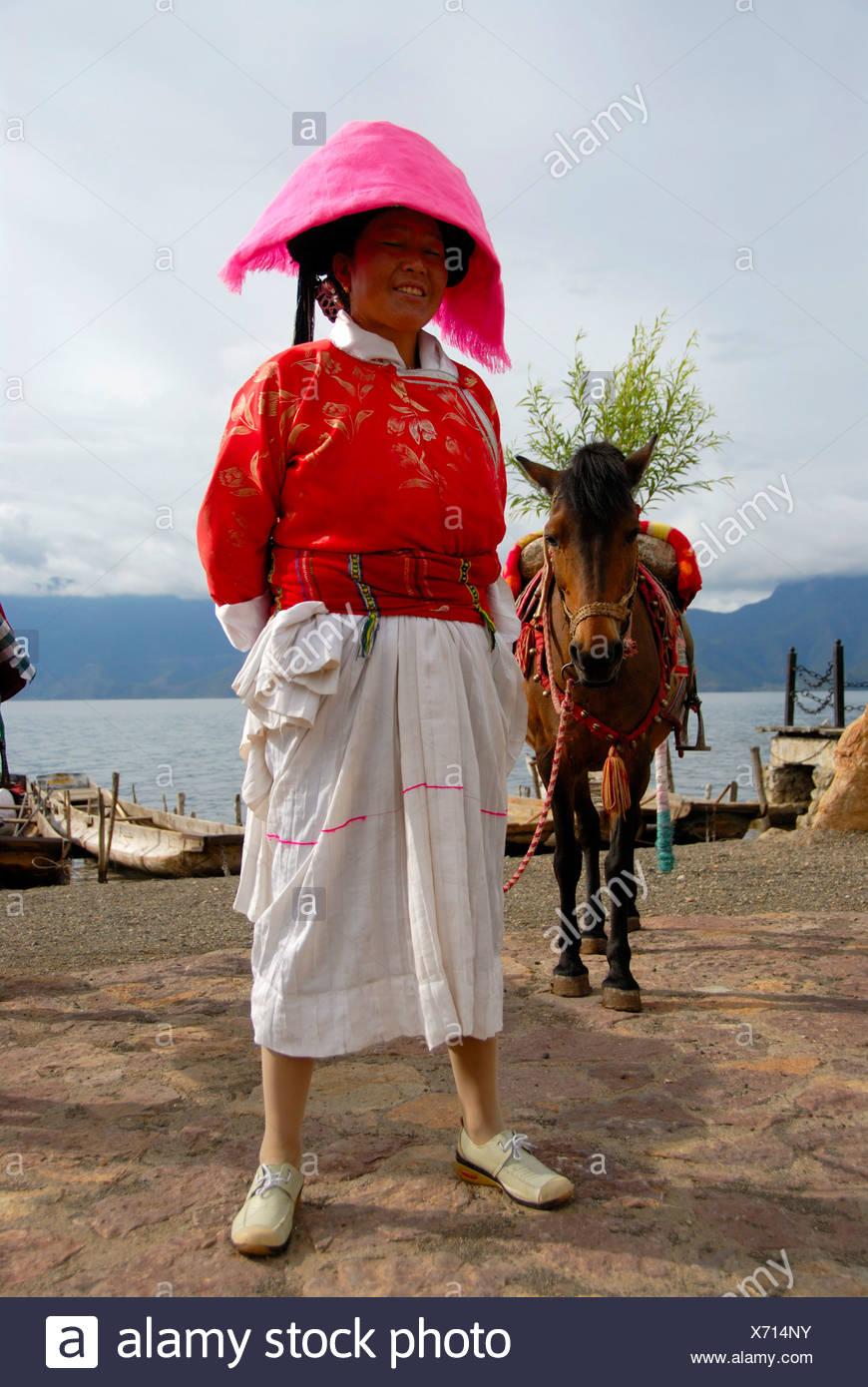 La etnología, mujer de la etnia Mosu vestidas en trajes tradicionales con el caballo, Luoshui, Lago Lugu Hu, provincia de Yunnan, Peopl Imagen De Stock