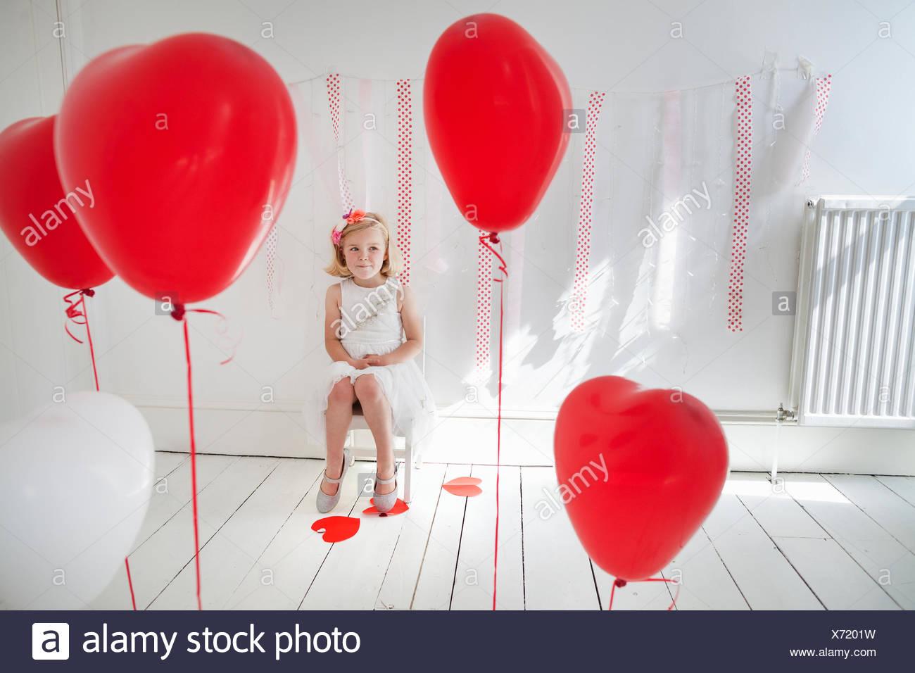 Chica posando para una foto en un estudio del fotógrafo, rodeado de globos rojos. Imagen De Stock