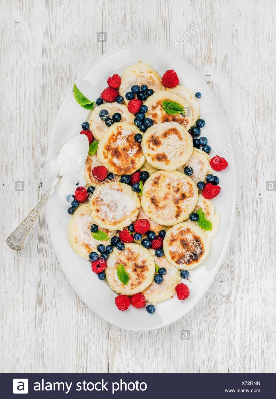 Syrniki o queso cottage panqueques con bayas frescas y salsa de crema agria en el plato para servir sobre fondo de madera blanca, Foto de stock