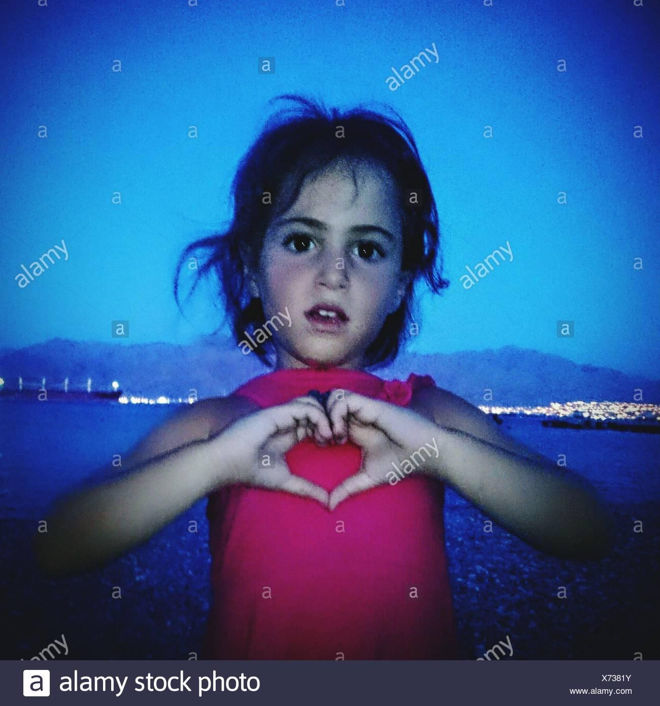 Retrato de linda chica mostrando Forma corazón por manos contra River Imagen De Stock