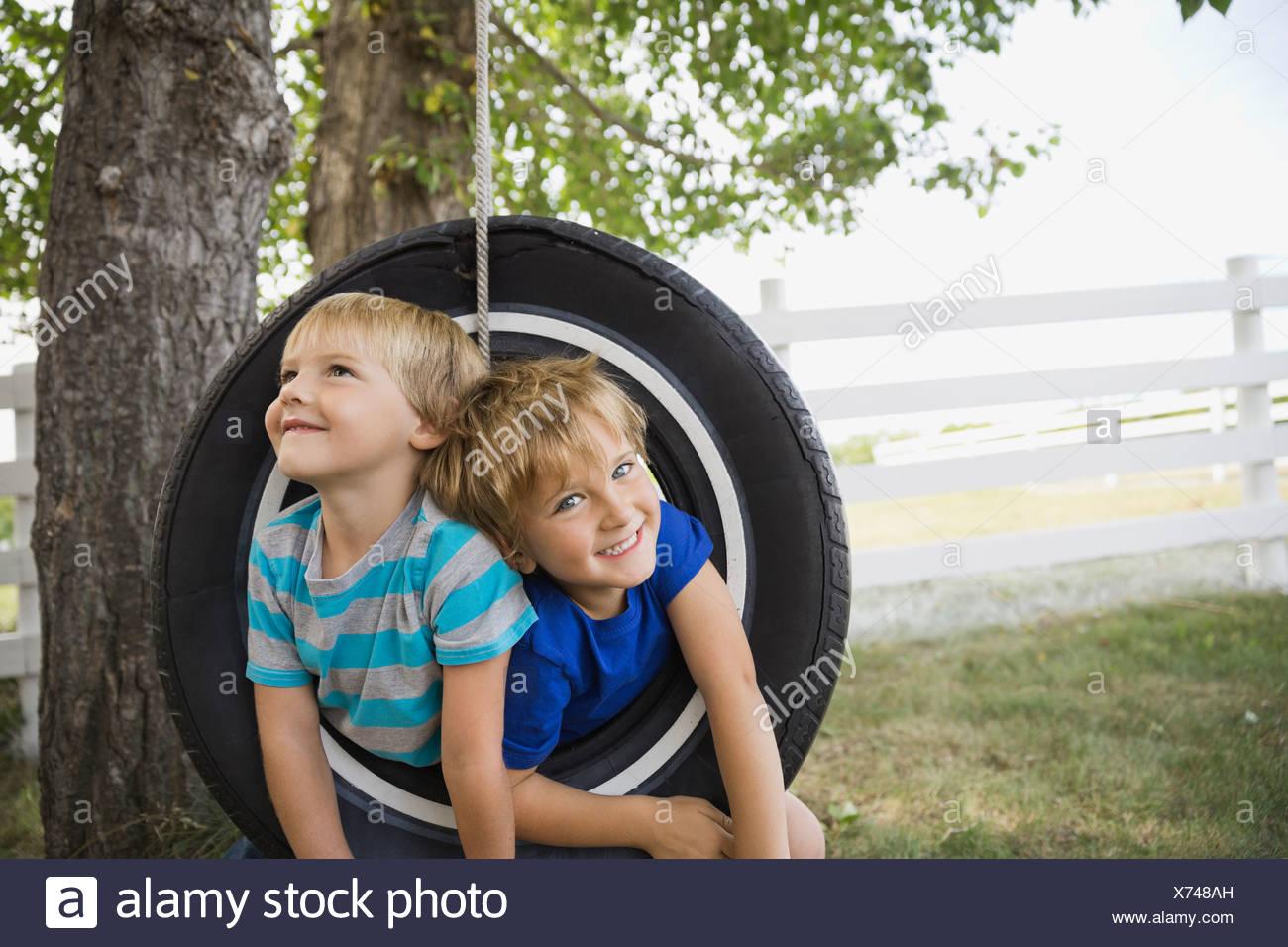 Los niños juguetones en un columpio de neumático Imagen De Stock