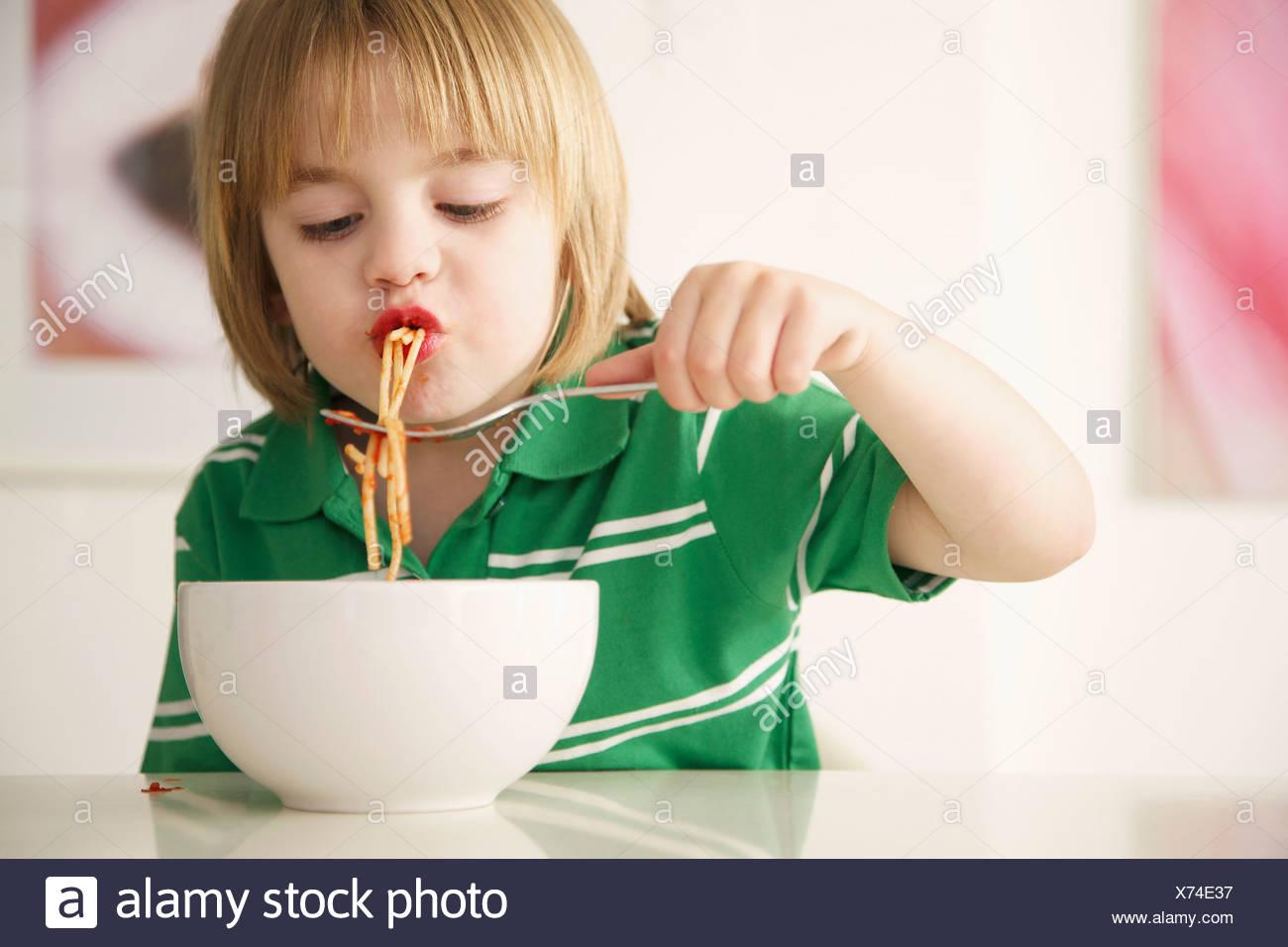 Un muchacho comiendo espaguetis Imagen De Stock