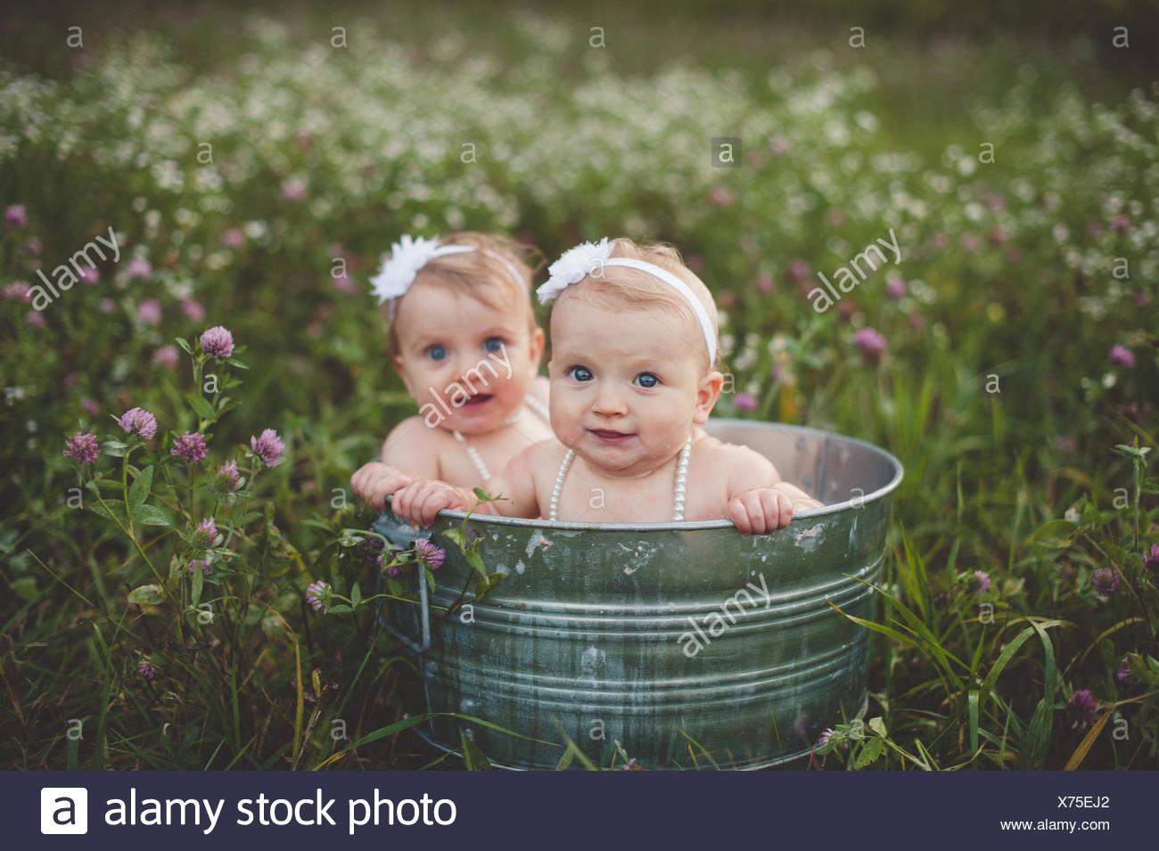 Retrato de bebé hermanas gemelas baño en una bañera de estaño en un prado de flores silvestres Imagen De Stock