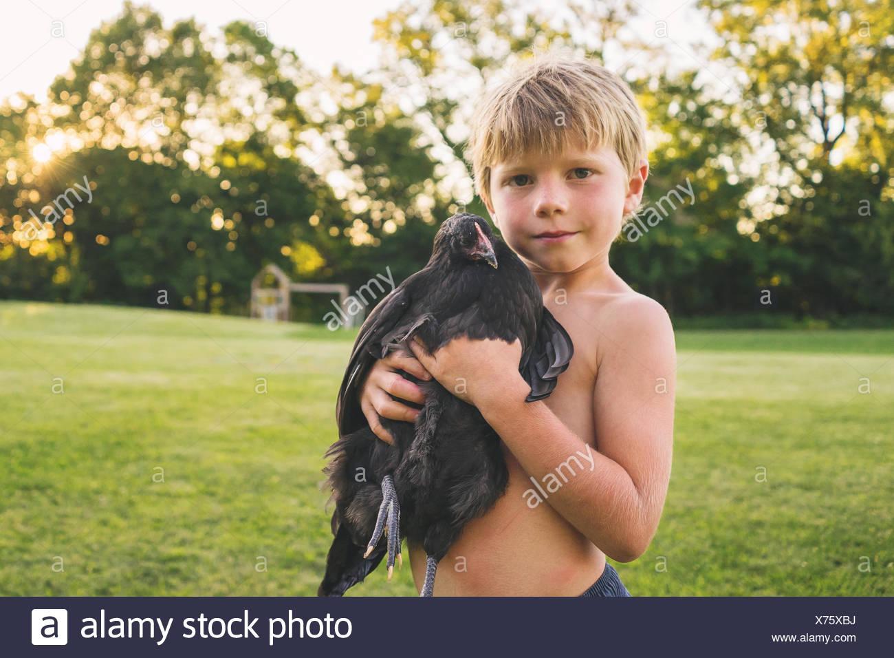 Retrato de un niño sosteniendo q pollo Imagen De Stock
