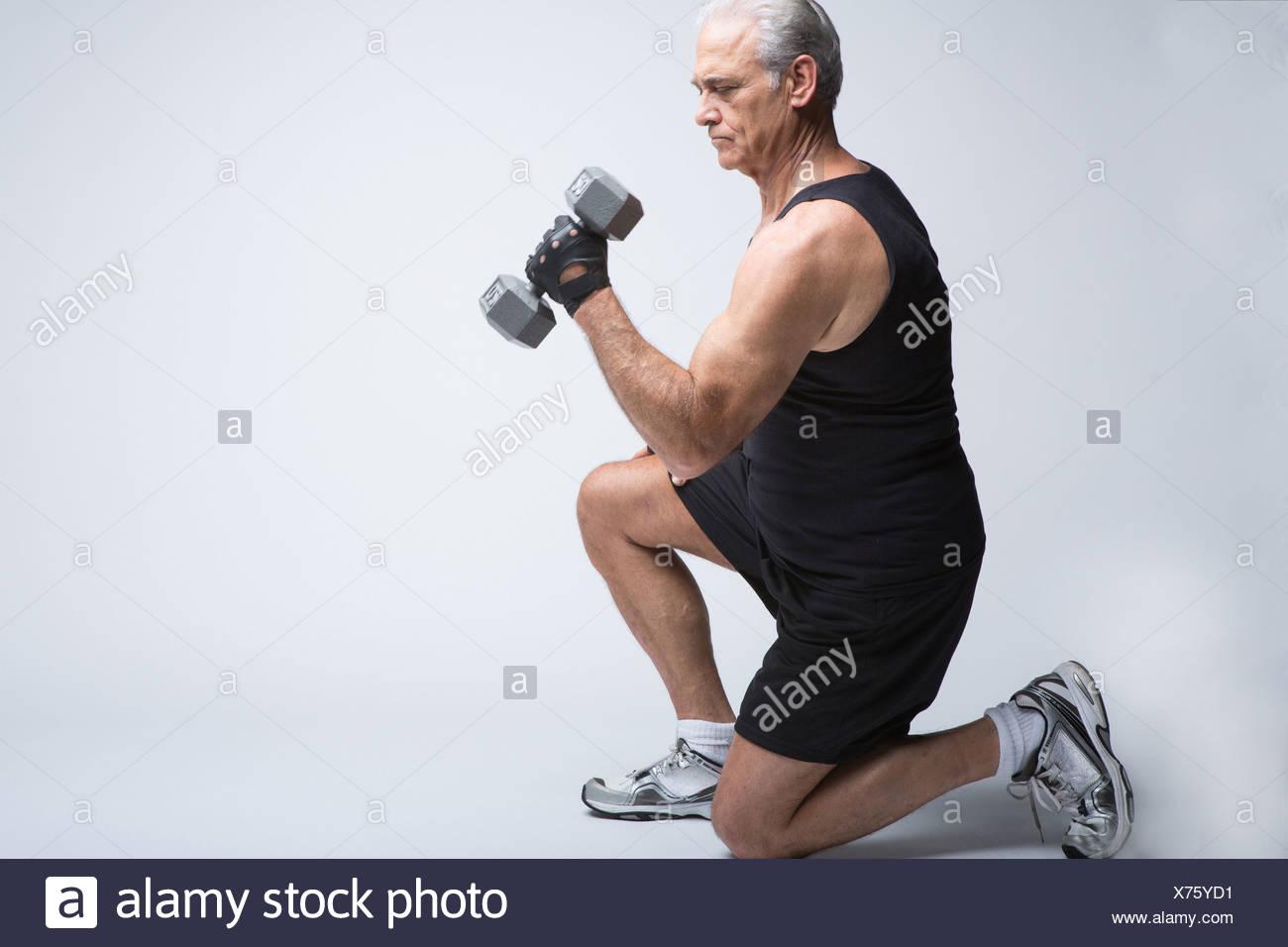 Hombre senior en ropa deportiva levantando el brócoli Imagen De Stock