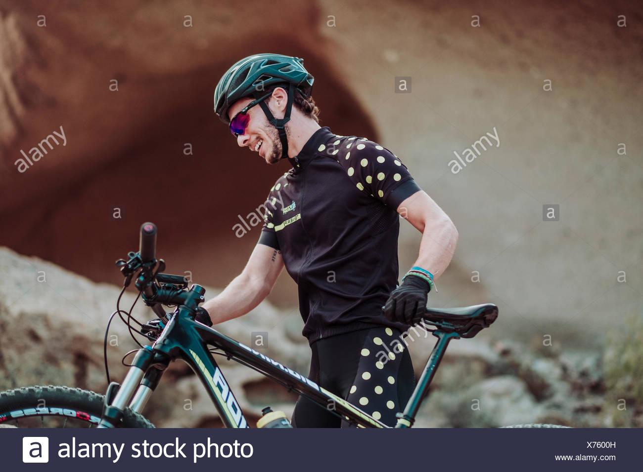 Hombre caminando en el desierto con su bicicleta de montaña, Tenerife, Islas Canarias, España Foto de stock