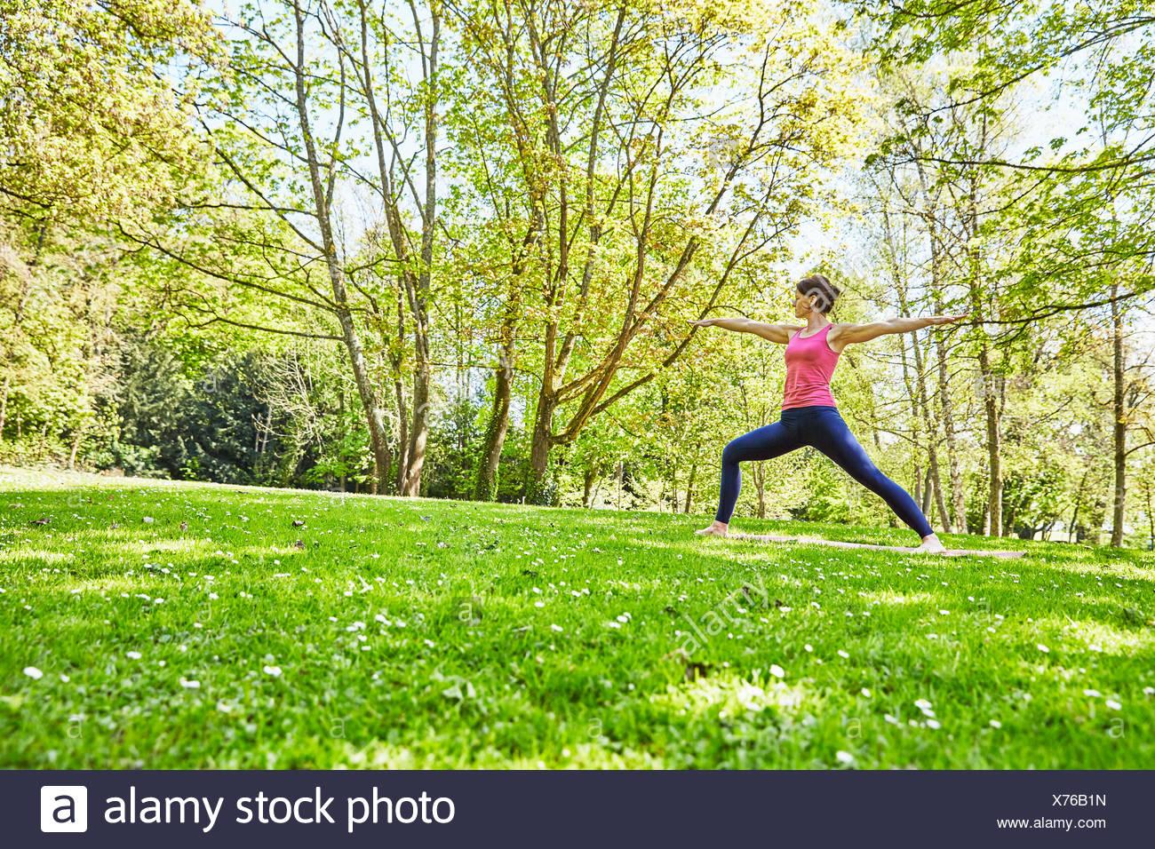 Mujer, brazos abiertos, las piernas en posición de yoga Imagen De Stock