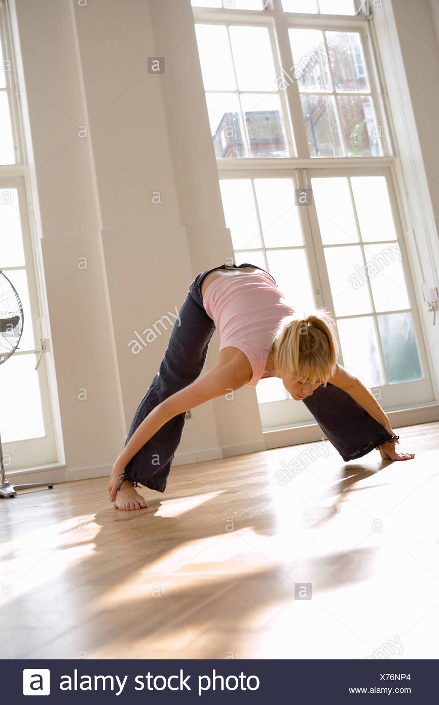 Mujer el ejercicio de tocar los dedos de los pies con piernas separadas vista frontal de la inclinación de la superficie nivelada Imagen De Stock