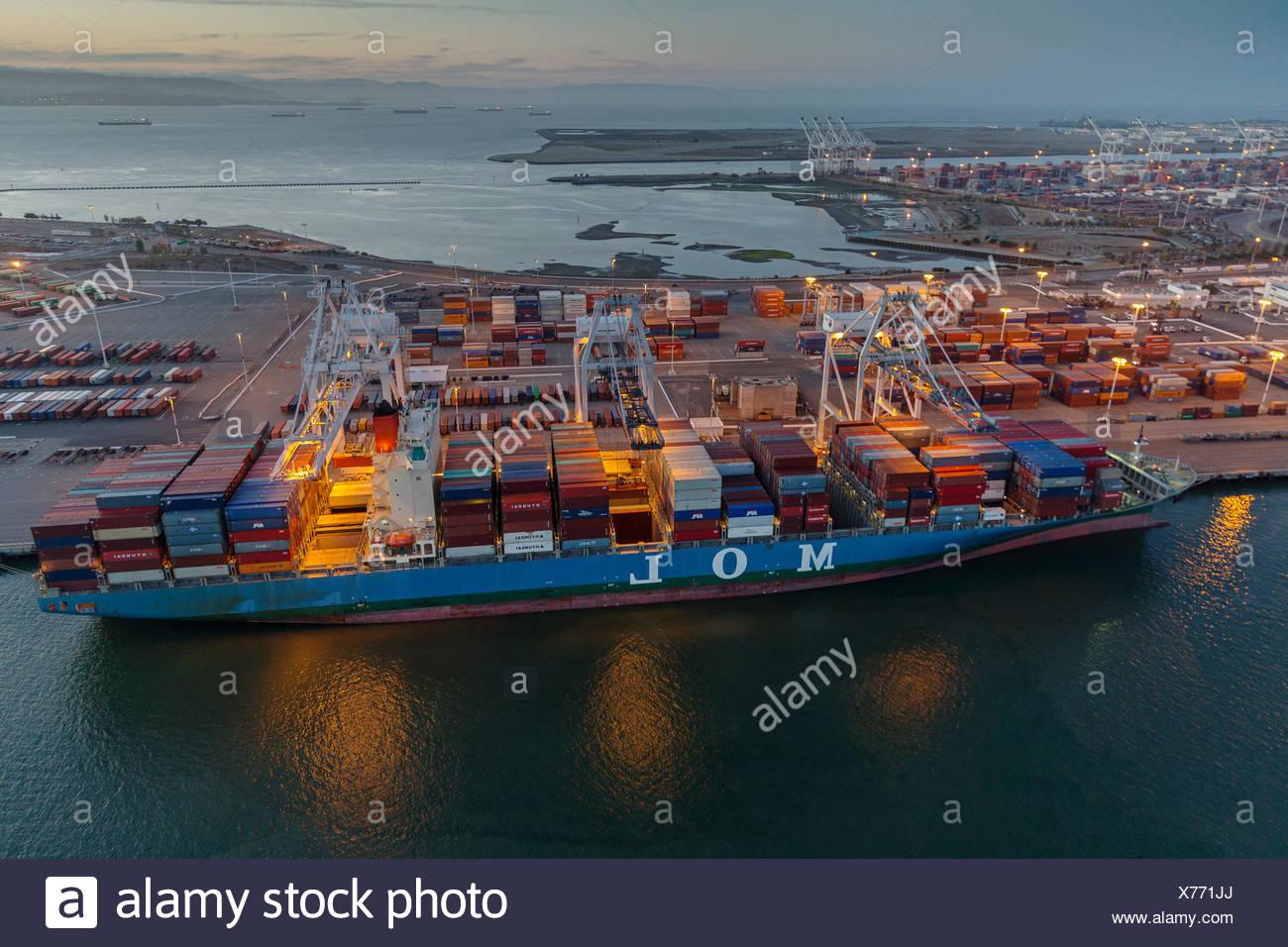 Muelle comercial con un buque portacontenedores al atardecer, Oakland, California, EE.UU. Foto de stock