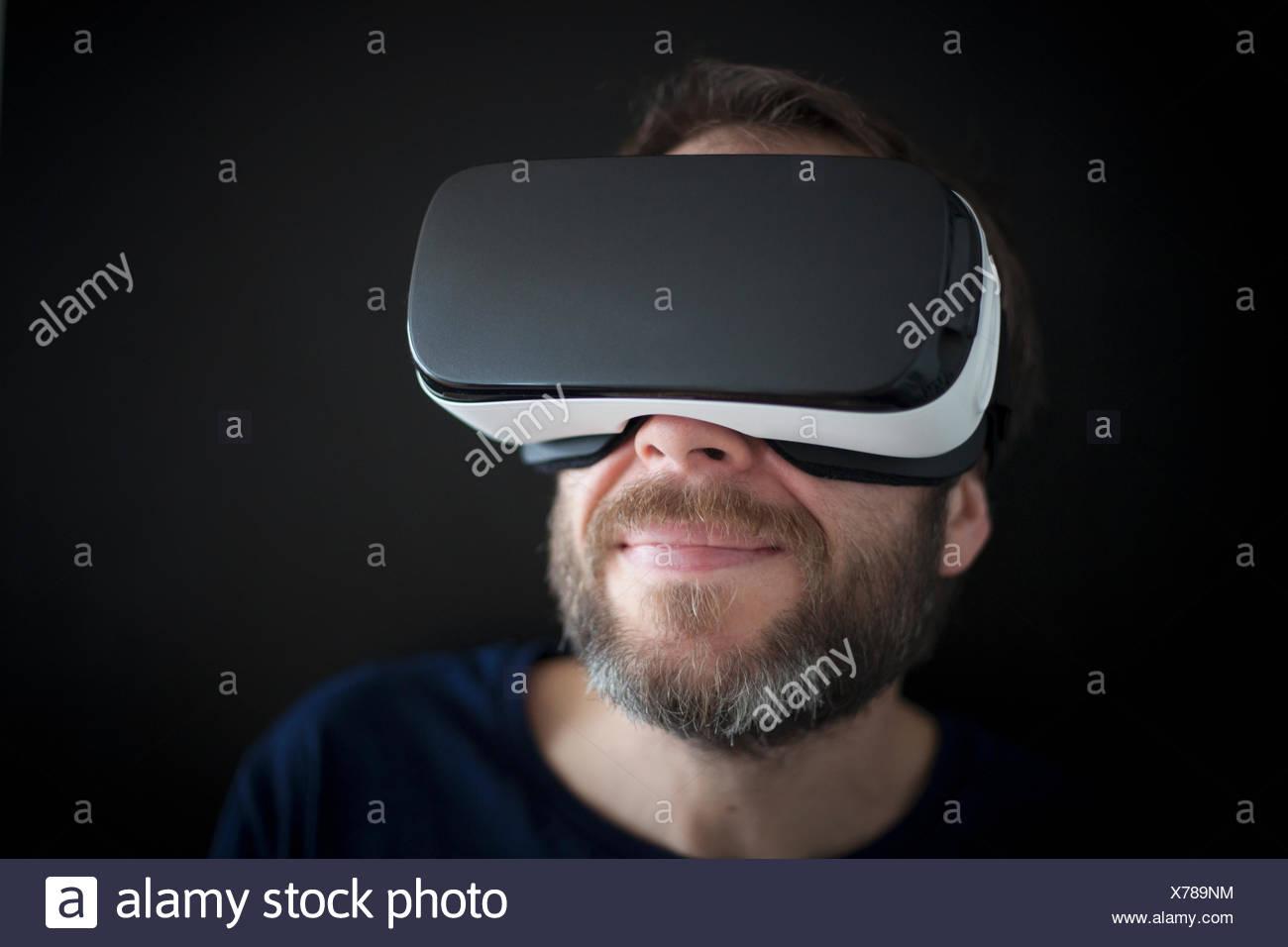 Hombre sonriendo portando gafas de realidad virtual Foto de stock