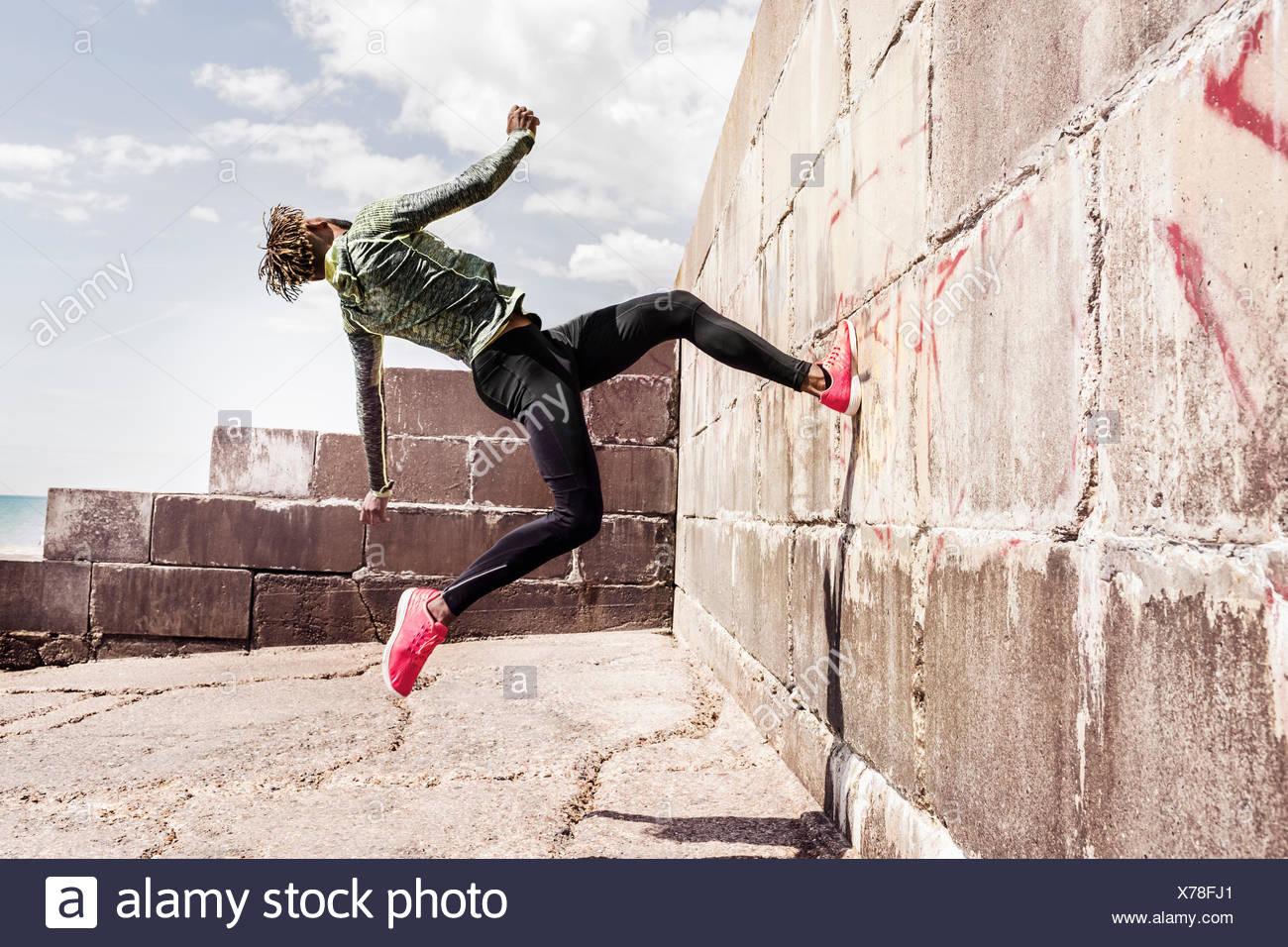 Joven, Free Running, al aire libre, corriendo hacia arriba de la pared lateral Imagen De Stock