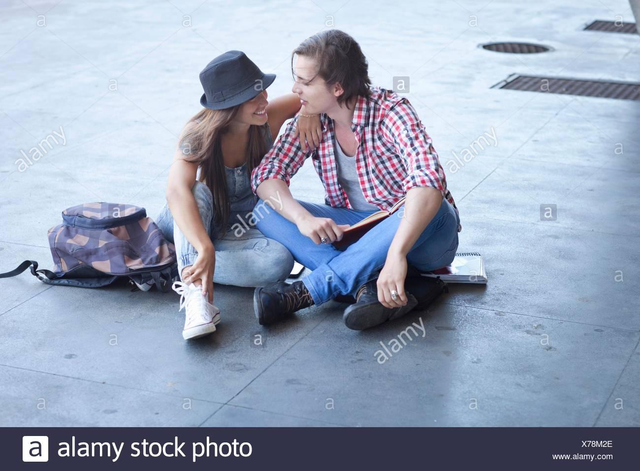 Pareja joven sentado en el suelo Foto de stock