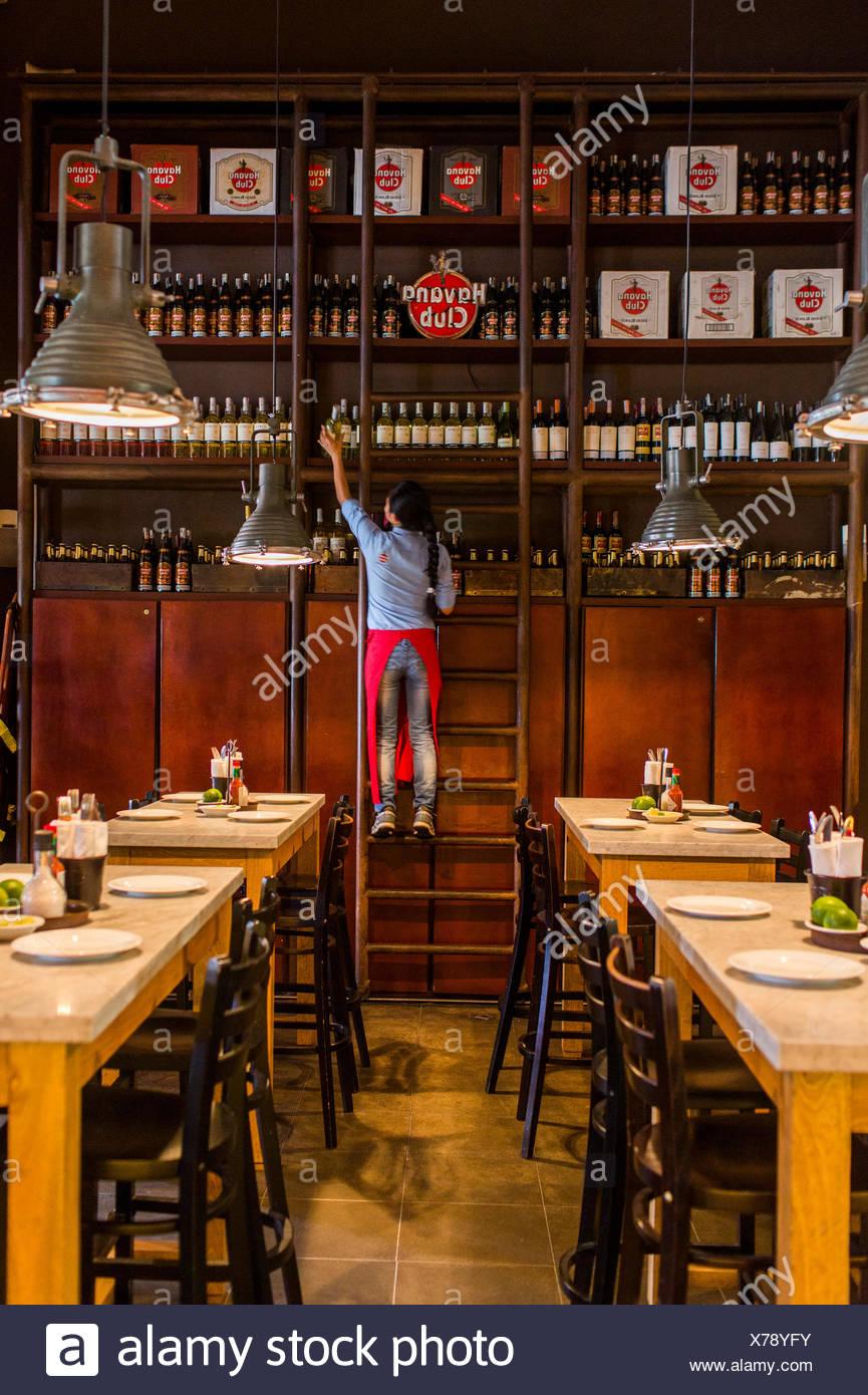Mujer tirando hacia abajo botella de ron en la central de cevicheria, restaurante en Bogotá, Colombia Imagen De Stock