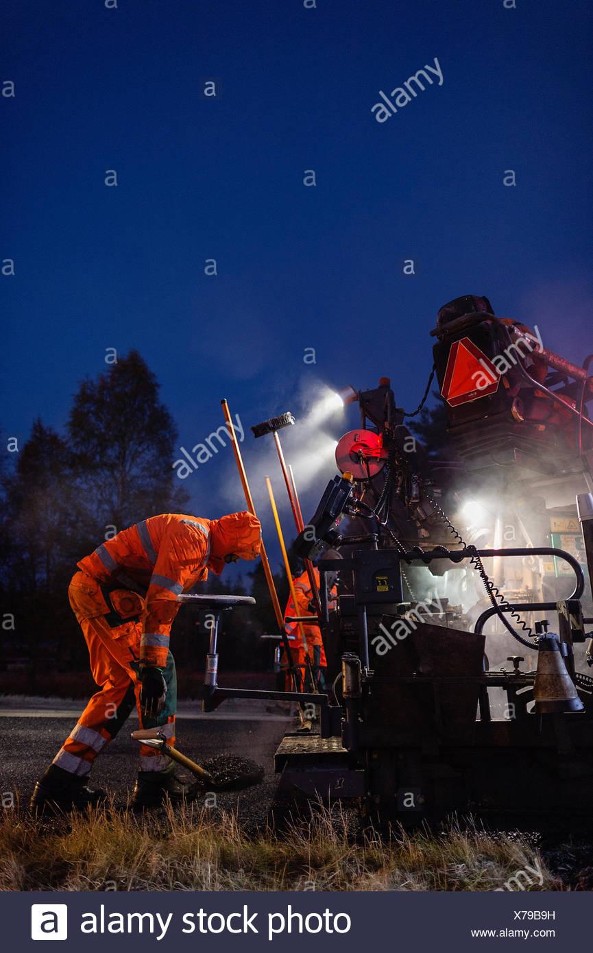 Suecia, Narke, dos trabajadores manuales reparación de carretera por la noche Imagen De Stock