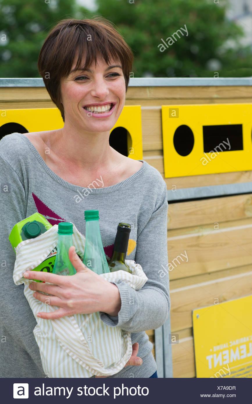 Mujer trayendo reciclables a centro de reciclaje Imagen De Stock