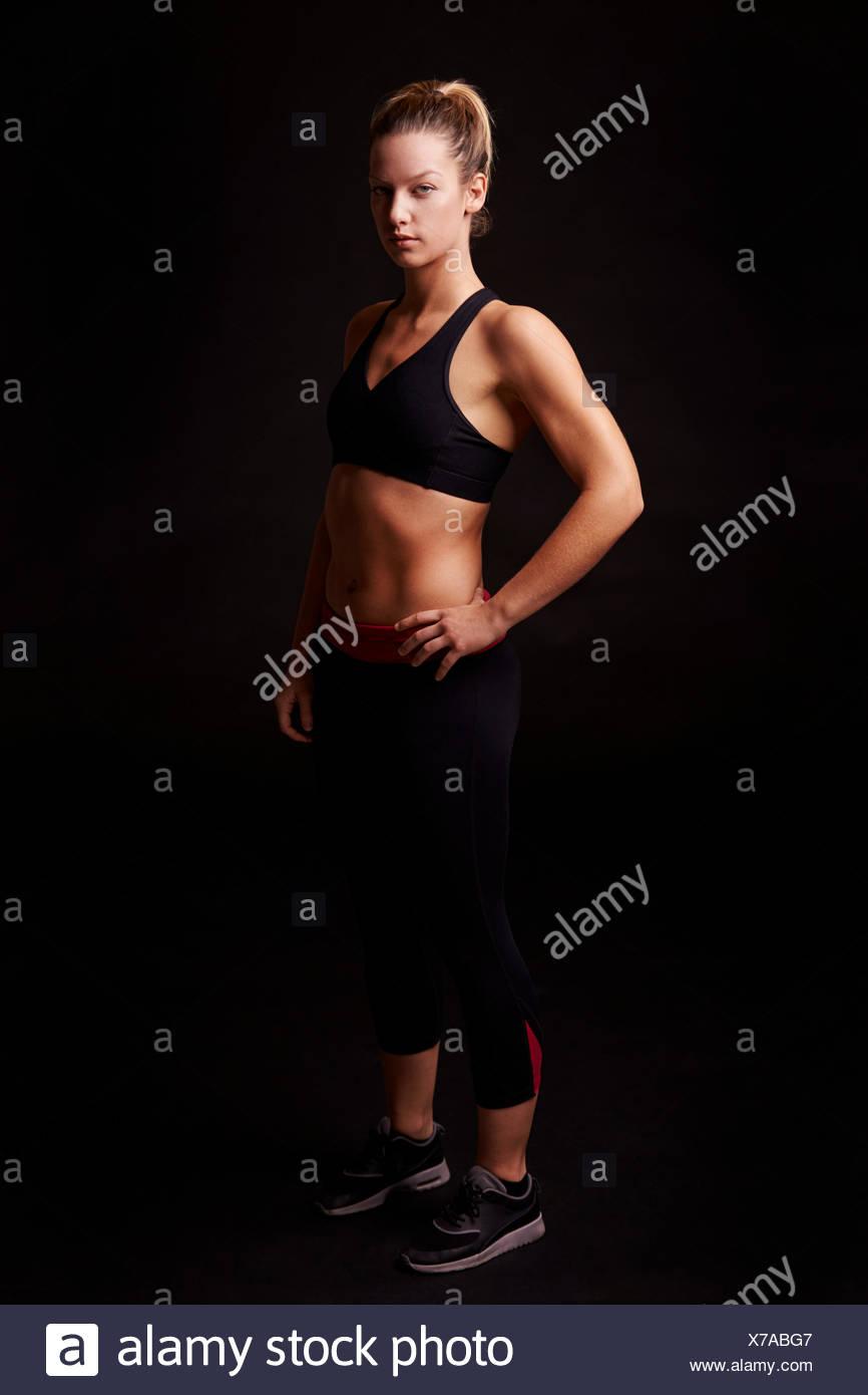 Athletic mujer rubia mirando a la cámara, longitud completa Imagen De Stock