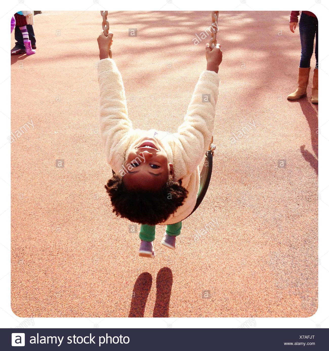 Retrato de una sonriente joven sentada en un columpio en el patio de recreo Imagen De Stock