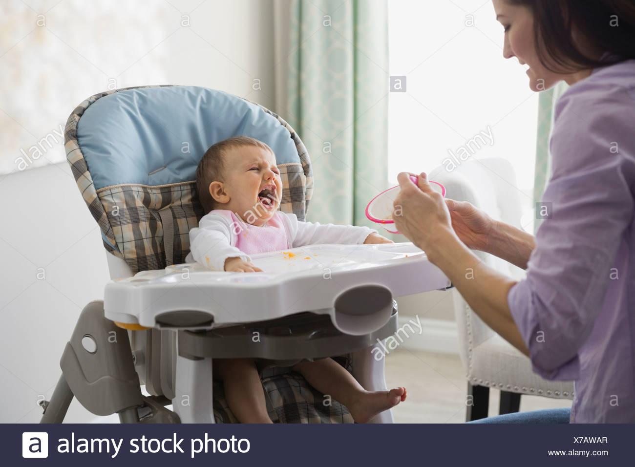 Madre alimentando el llanto del bebé en casa Imagen De Stock