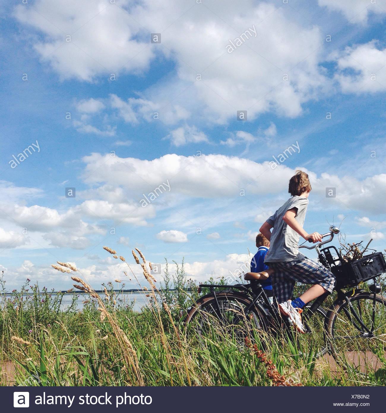 Países Bajos, dos chicos (10-11) ciclismo cerca del mar Imagen De Stock