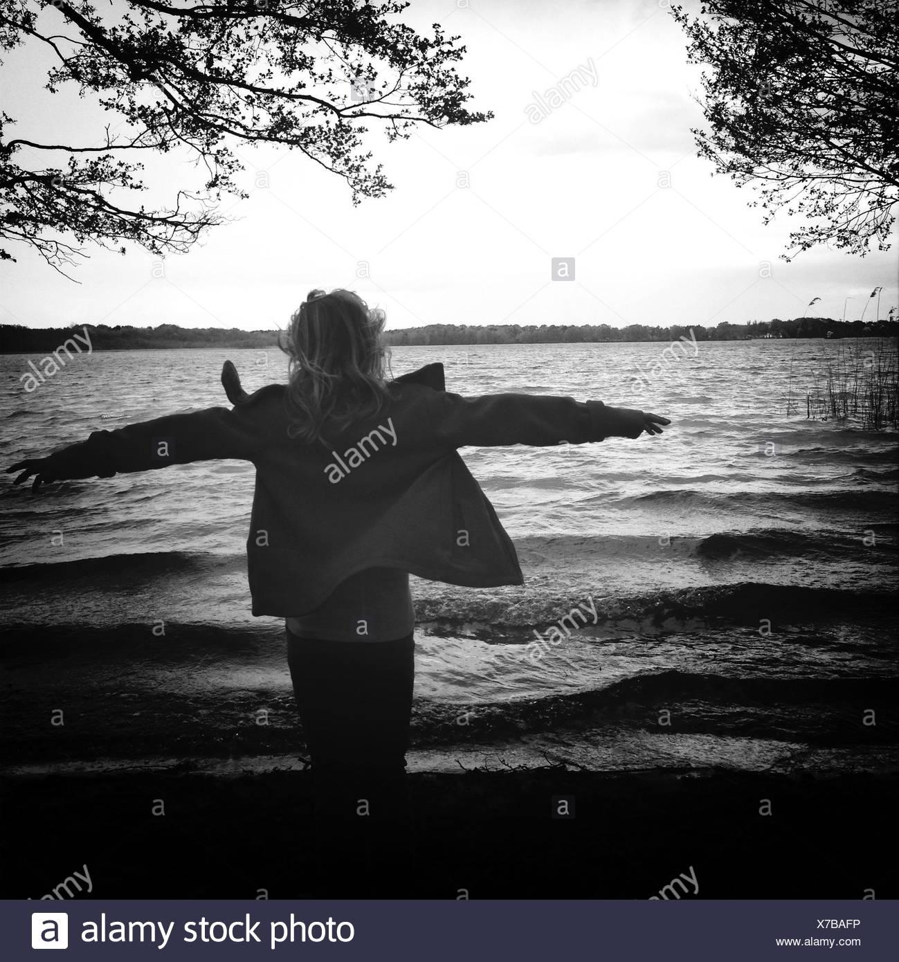 Vista trasera de la mujer disfruta el viento en la orilla Imagen De Stock
