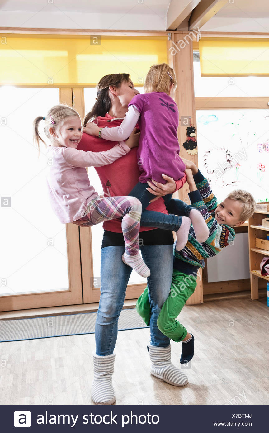 Educador hembra arrasar con tres niños en kindergarten. Imagen De Stock