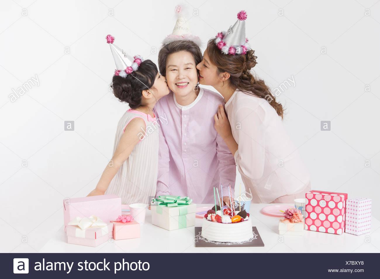 Madre E Hija Besar A La Abuela Sonriendo Todo En Sombreros De Fiesta
