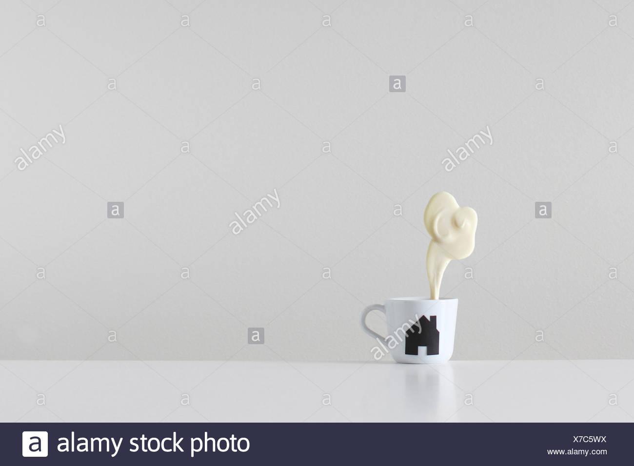Home brew, taza de té con la silueta de la casa de vapor e impresión hecha de chocolate blanco procedente de la chimenea. Imagen De Stock