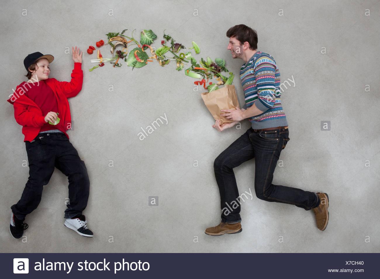 El hombre y el muchacho equilibrando las verduras Imagen De Stock