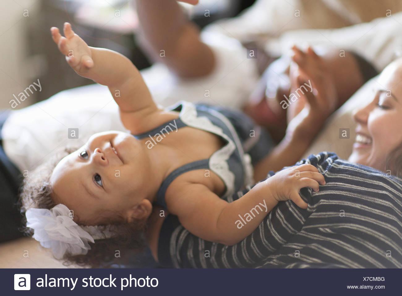 La madre y el padre tumbado en la cama con su bebé hija Imagen De Stock