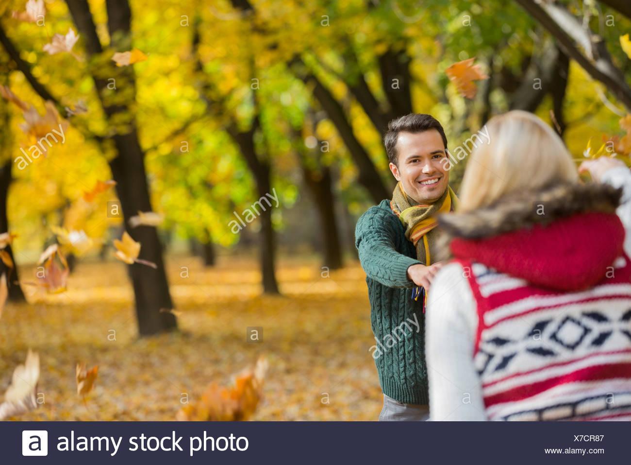 Pareja feliz jugando con las hojas de otoño en el parque Foto de stock