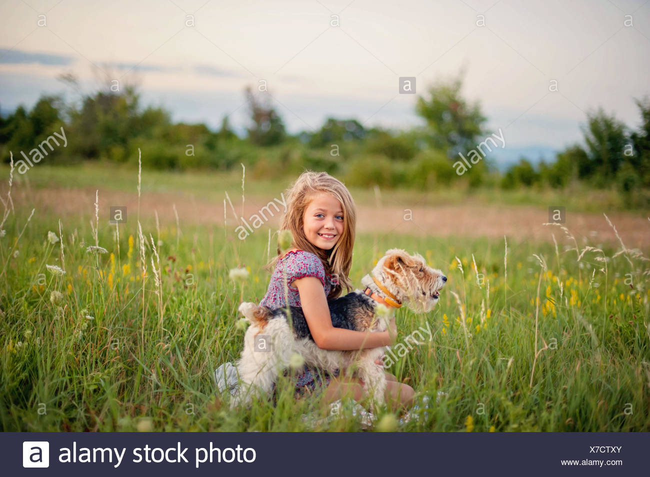 Retrato de una sonriente joven sentada en el campo abrazando a su perro Fox Terrier Imagen De Stock