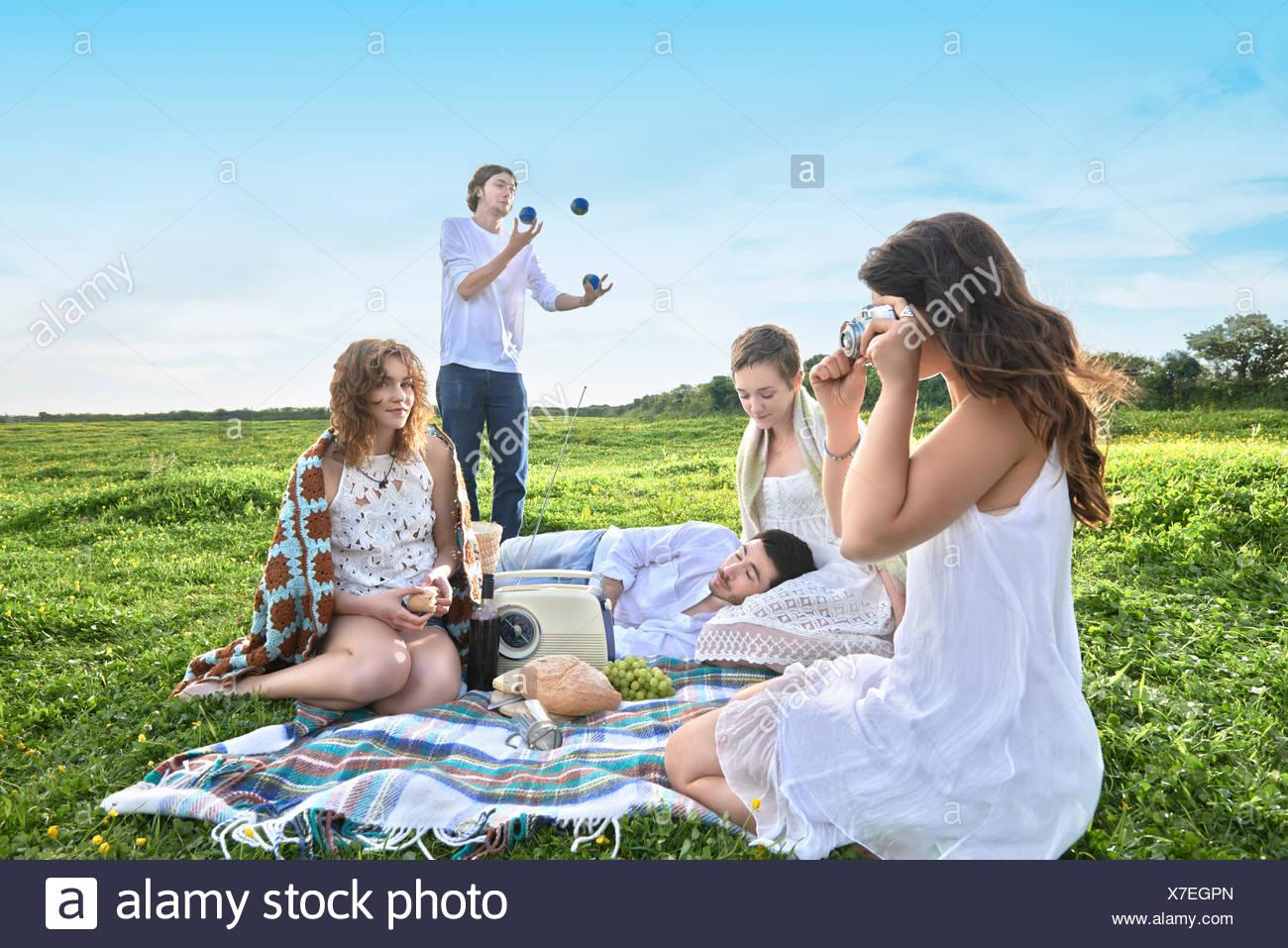 Grupo de amigos adultos jóvenes haciendo un picnic en el campo Foto de stock