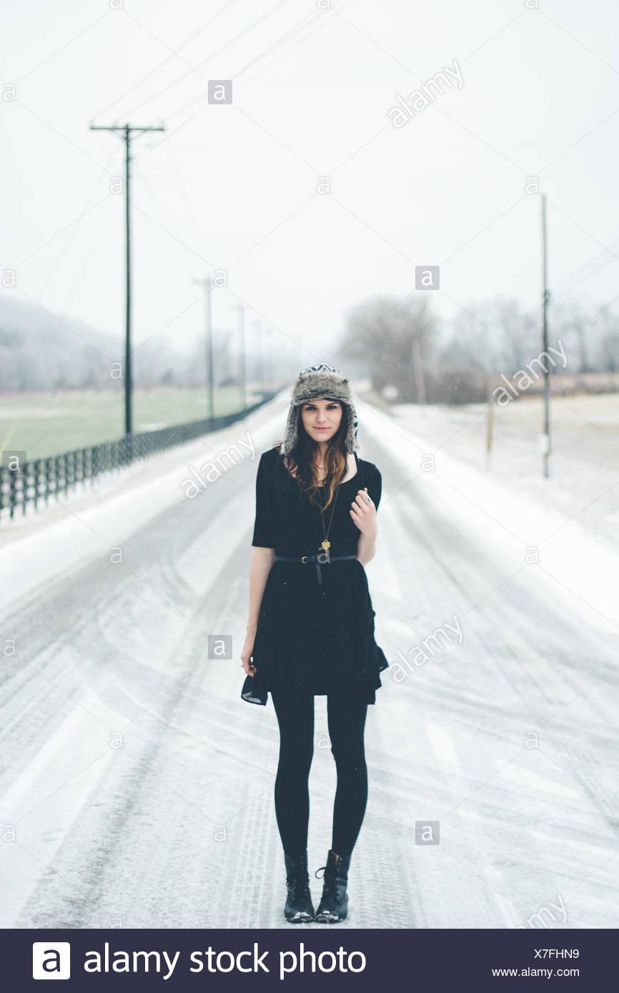 Mujer joven de pie en la carretera en invierno Imagen De Stock