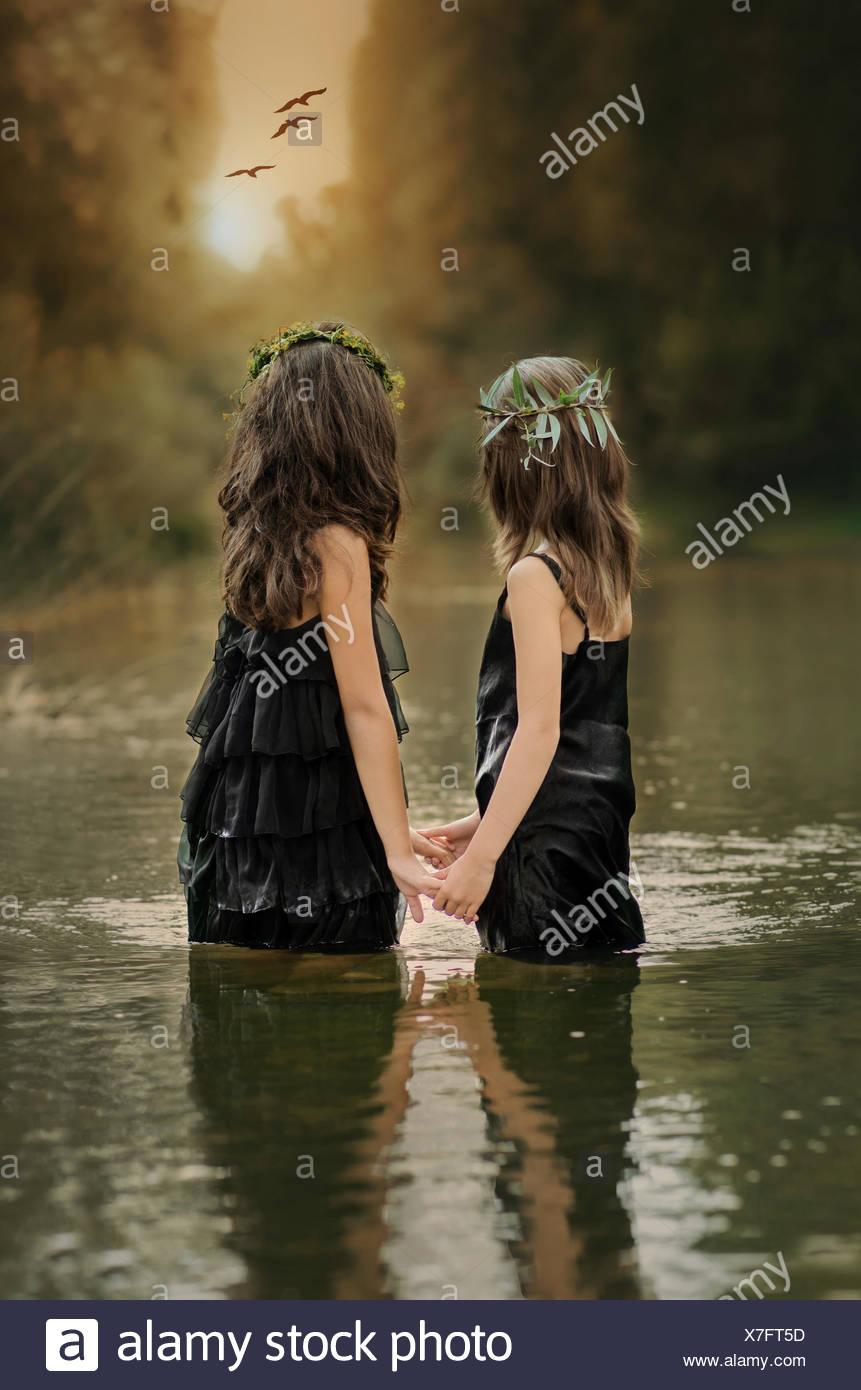 Dos niñas (8-9, 10-11) tomados de la mano y observar el atardecer Imagen De Stock