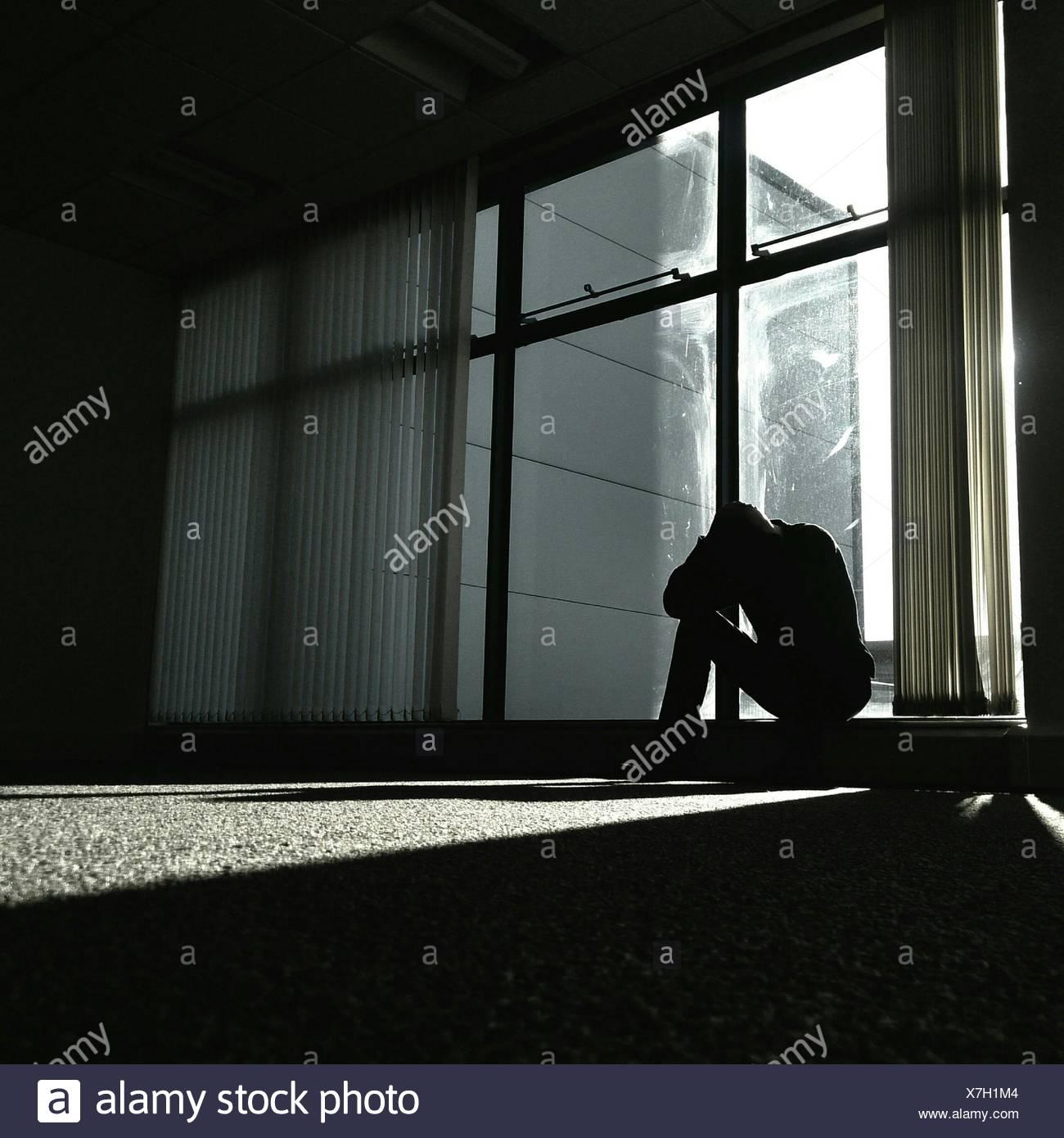 Pisado hombre sentado por la ventana de cristal en el hogar Imagen De Stock
