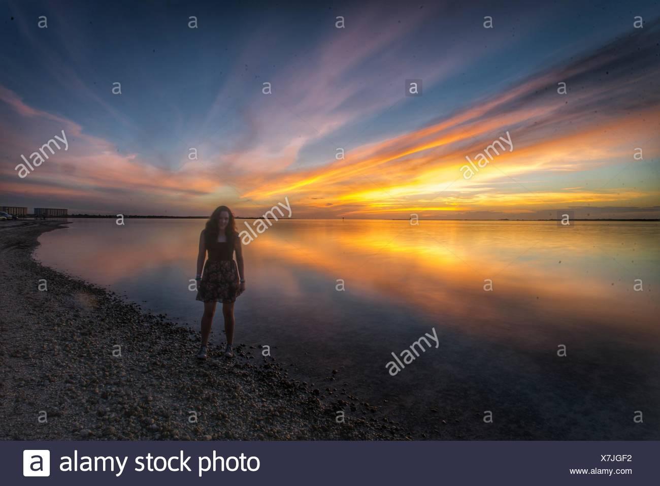 La longitud completa de la Mujer de pie en la playa al anochecer Imagen De Stock