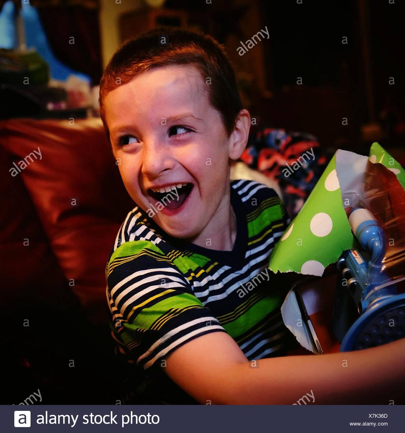 Muchacho feliz con la boca abierta la celebración don mientras está sentado en el sofá en casa Foto de stock
