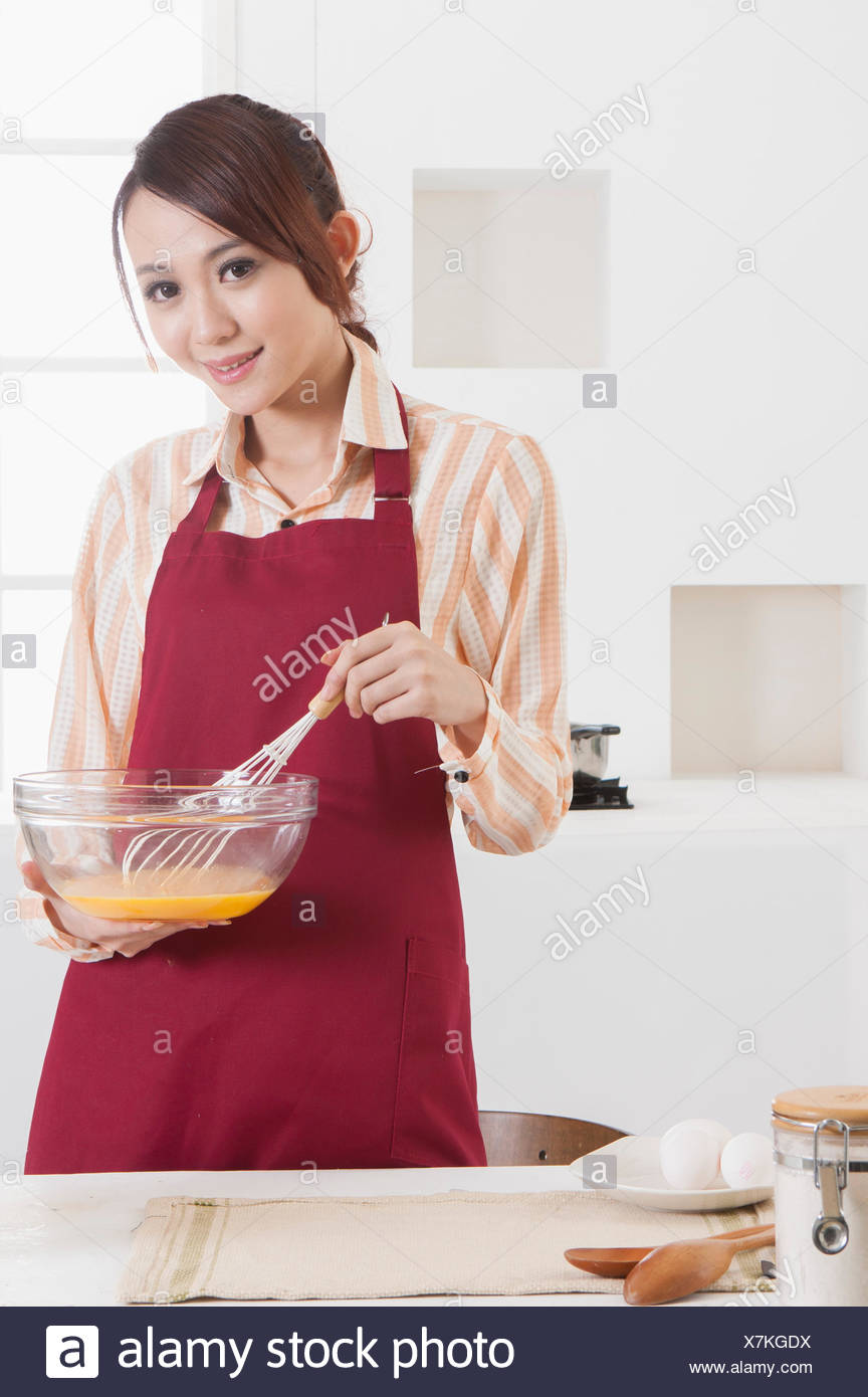Mujer joven sujetando el cable batidor de huevos y sonriendo a la cámara. Foto de stock
